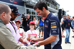 Mark Webber, Red Bull Racing signs autographs for the fans.