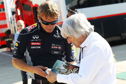 Bernie Ecclestone, CEO Formula One Group, signs an autograph for a Red Bull Racing team member