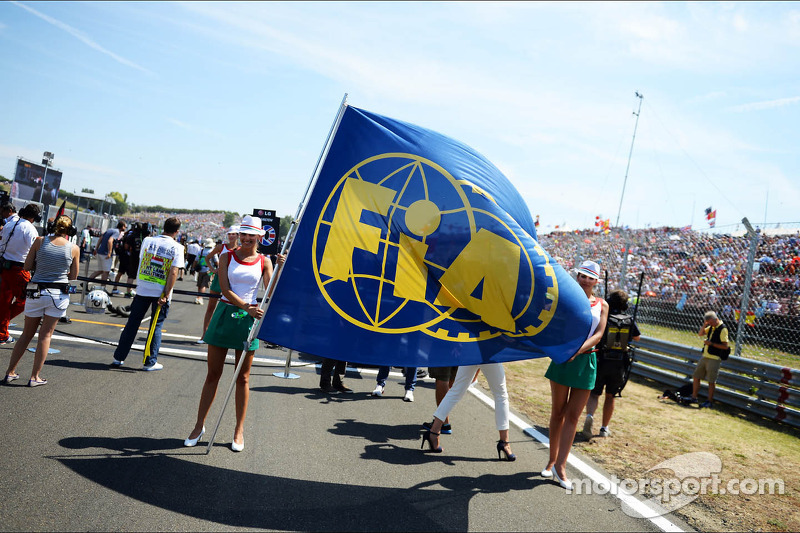 Grid girls with the FIA Flag