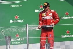 Third place Kimi Raikkonen, Ferrari celebrates on the podium with the champagne