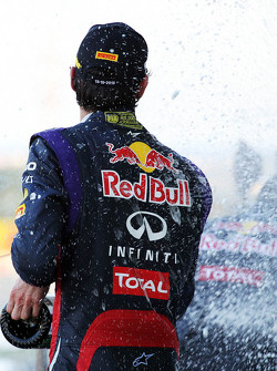 Mark Webber, Red Bull Racing celebrates his second position with the champagne on the podium