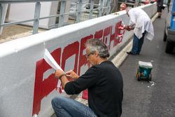 Trabalhadores preparando pintura da Porsche no pit wall