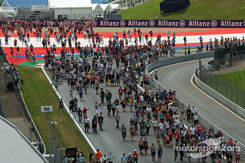 Fans stream down the start / finish straight