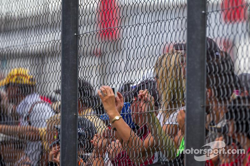 Fan scatta una foto attraverso la recinzione