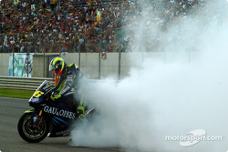 Race winner Valentino Rossi celebrates with a burnout