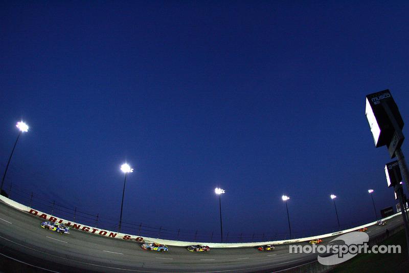 Race action under the lights at Darlington Raceway