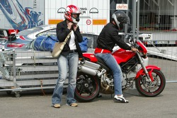 Michael Schumacher arrives at the track on a Ducati