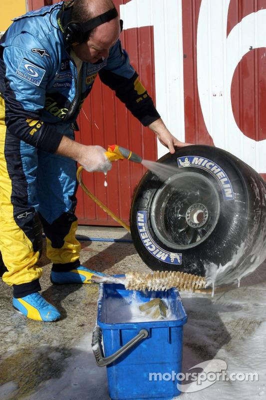 Un membre de l'équipe Renault nettoie les pneus