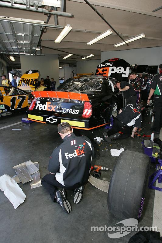 Des membres de l'équipe FedEx Chevy réparent la voiture numéro 11 de Denny Hamlin