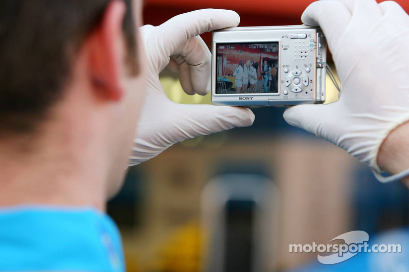 Un membre de l'équipe Renault F1 prend en photo des jeunes femmes de Telefonica sur la ligne des stands