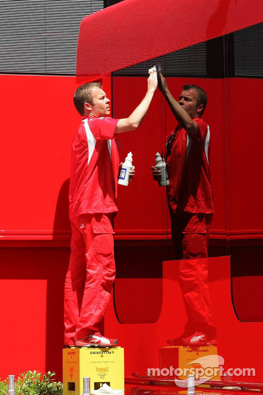 Un membre de l'équipe Scuderia Ferrari nettoie les camions