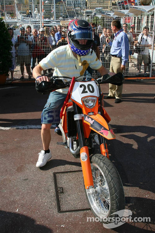 Scott Speed conduit une moto dans le paddock