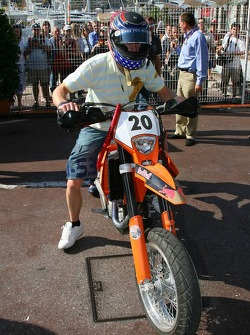 Scott Speed rides a motocross bike in the paddock
