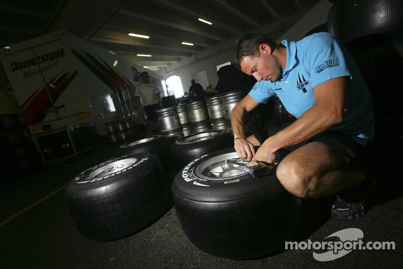 Un membre de l'équipe Trident Racing vérifie les pneus