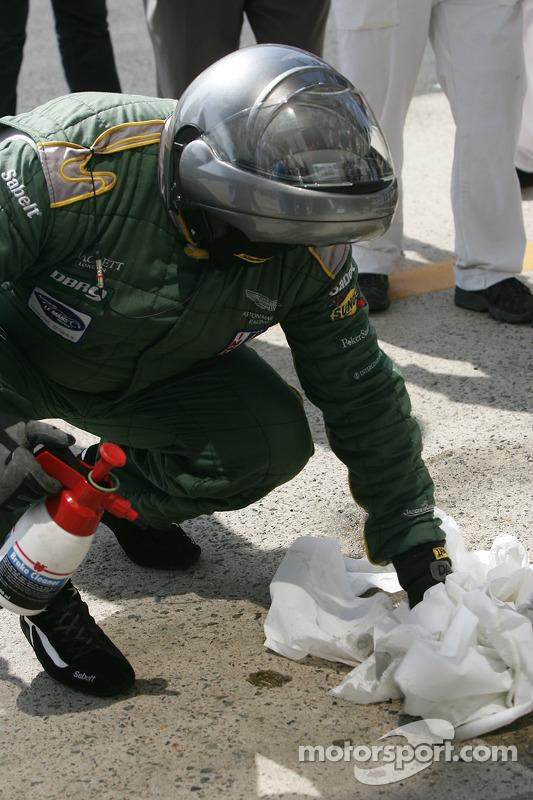 Les membres de l'équipe Aston Martin Racing nettoient le stand