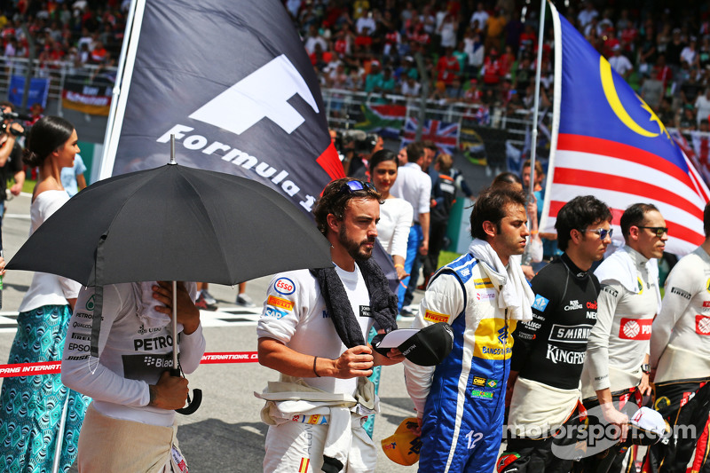 Lewis Hamilton, Mercedes AMG F1, dan Fernando Alonso, McLaren as the grid observes the national anth