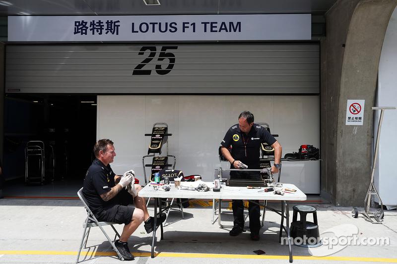 Mecánicos del Lotus F1 trabajan en el pit lane