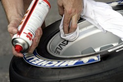 A Red Bull Racing crew member cleaning Michelin tyres