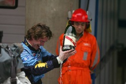 A Renault mechanic holds a broken bottle of champagne