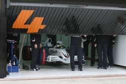 BMW Sauber team members open the garage door