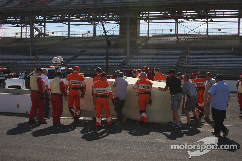 Workers replace the pitwall barrier after Піппа Манн's crash