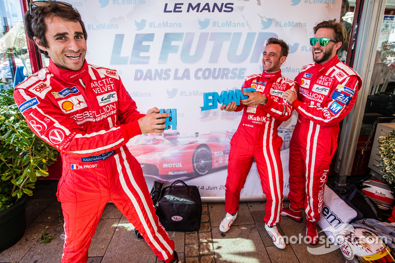 Rebellion Racing: Nicolas Prost and Mathias Beche break the #LEMANS sign while Nick Heidfeld looks o