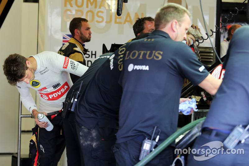 Romain Grosjean, Lotus F1 Team helps clean his Lotus F1 E23 after a trip through the gravel trap