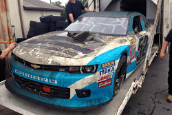 The burned hauler of Jimmy Means Racing carrying the car of Joey Gase