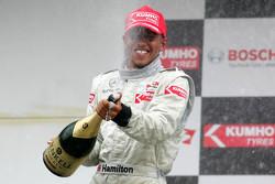 Podio: terzo posto Lewis Hamilton spruzza champaign