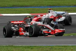 Heikki Kovalainen, McLaren Mercedes leads Jarno Trulli, Toyota Racing