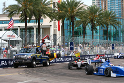 The field goes by as the wrecker brings in the car of Arie Luyendyk Jr.