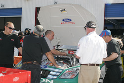 A NASCAR official inspects motors