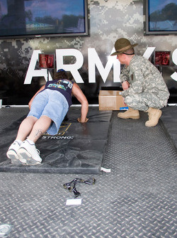 Fans at the Army trailer trry to win prizes by doing as many push ups as they can can