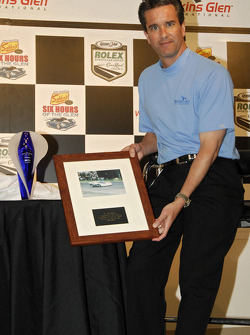 Craig Rust shows the framed piece that goes with the award