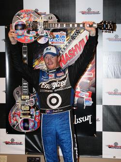 Victory lane: Scott Dixon raises his guitar triumphantly