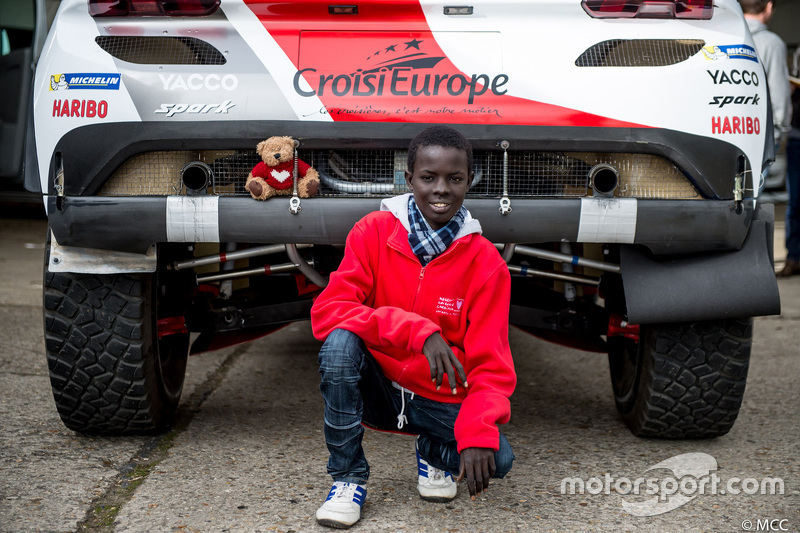 Samba, a Senegalese boy who was saved thanks to Mécénat Chirurgie Cardiaque, with the Peugeot 2008 DKR15+ of Romain Dumas and François Borsotto