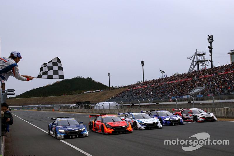Takuma Sato agita bandeira quadriculada para carros da Super GT
