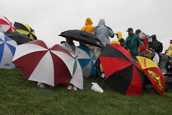 Umbrellas open up as the rain starts to fall