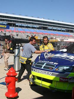 Robby Gordon inspects his damaged race car