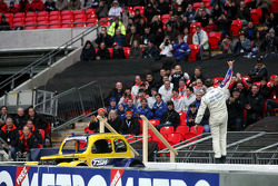 Terry Grant waves to the crowd as his Legend spins on the track