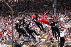 Race winner Helio Castroneves climbs the fence with his Penske team