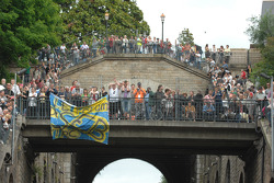 Fans look out apartment windows at the drivers parade
