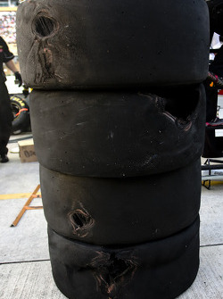 Brad Keselowski's torn up tires sit on pit road after he and Denny Hamlin have contact
