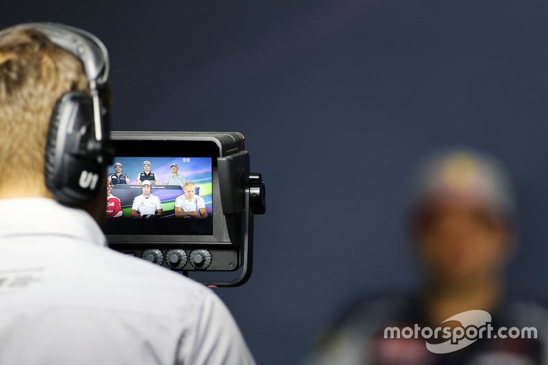 Carlos Sainz al fondo desenfocado durante una rueda de prensa en la que también está presente Fernando Alonso